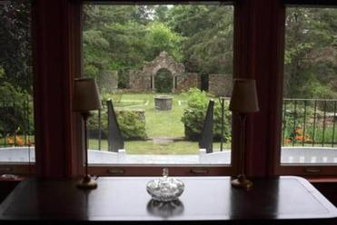 A view from the inside of the home looking out at the original 1930s stone architecture in the garden.